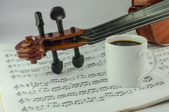 Violin and cup of coffee on music sheet. Closeup od violin and cup of coffee on music sheet background Stock Image