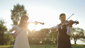 Violin duet man and woman play violin on nature at the sunset stock video
