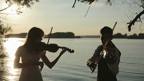 Violin duet man and woman play violin on nature at the sunset.  stock video