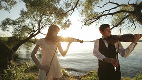 Violin duet man and woman play violin on nature at the sunset on the lake stock video