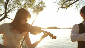 Violin duet man and woman play violin on nature at the sunset on the lake.  stock footage