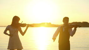 Violin duet man and woman play violin on nature at the sunset on the lake stock footage