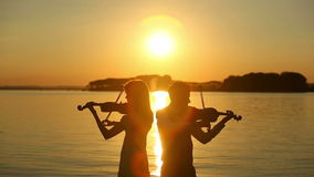 Violin duet man and woman play violin on nature at the sunset on the lake.  stock video footage