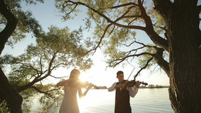 Violin duet man and woman play violin on nature at the sunset on the lake. HD shot with slider stock video