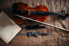 Violin, fiddlestick, notes and bowties closeup Stock Images