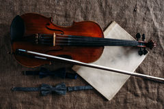 Violin, fiddlestick, notes and bowties closeup Royalty Free Stock Images