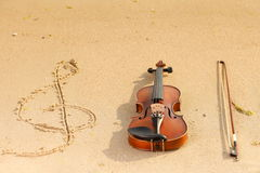 Violin and g clef on beach. Music concept Royalty Free Stock Photos