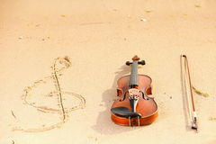 Violin and g clef on beach. Music concept Stock Photography