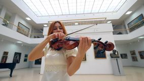 Violin is getting played by a female musician in a white dress stock video footage