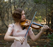 Violin Girl at Dusk. Pretty young woman playing the violin in a forest wearing a pink vintage evening gown. Short depth of field stock photos