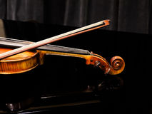 Violin on the grand piano in  a concert hall Stock Images