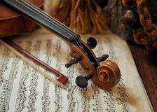 Violin head and bow on sheet music Stock Photo