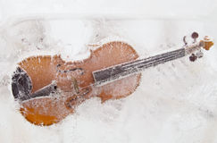 Violin into the ice. Violin with broken strings frozen into the ice. Close-up Royalty Free Stock Photo