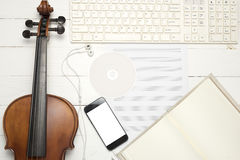 Violin with keyboard computer music paper note dvd disc and smar. T phone on white wood background Royalty Free Stock Photo
