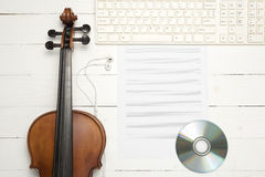 Violin with keyboard computer music paper note and dvd disc. On white wood background Stock Image