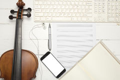 Violin with keyboard computer music paper note notebook and smar. T phone on white wood background Royalty Free Stock Images
