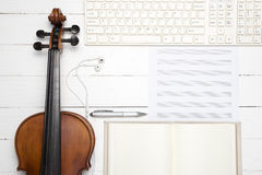 Violin with keyboard computer music paper note and notebook. On white wood background Royalty Free Stock Photography