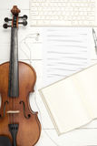 Violin with keyboard computer music paper note and notebook Royalty Free Stock Images