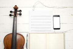 Violin with keyboard computer music paper note and smart phone. On white wood background Royalty Free Stock Photo