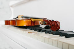 The violin and keyboard of white piano Stock Image