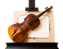 Violin laying on painting easel isolated. Old violin laying on painting easel isolated on white Stock Images