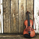 A Violin leaning on a wooden fence Stock Photography