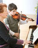 Violin lesson. Child playing the violin with his teacher on the piano royalty free stock images