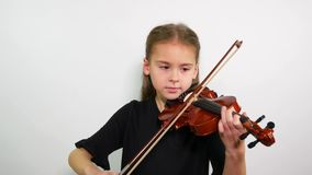 Violin lesson. The face of a girl playing a violin song.  stock video footage