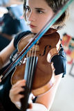 Violin Lesson or Practice. Pretty teenage girl/young woman playing the violin; closeup shot, soft focus, short depth of field stock image