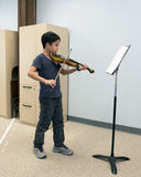 A violin lesson. A ten year-old boy stands playing the violin as he looks at the music on the stand in front of him.  He is taking a lesson and appears to be Stock Photos