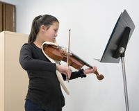 A violin lesson. A twelve year-old girl stands playing the violin as she looks at the music on the stand in front of her.  She is taking a lesson and appears to Royalty Free Stock Photos