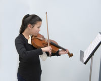 A violin lesson. A twelve year-old girl stands playing the violin as she looks at the music on the stand in front of her.  She is taking a lesson and appears to Stock Image