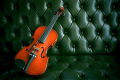 Violin on luxury green  leather sofa Royalty Free Stock Photo