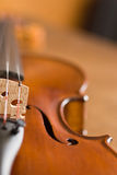 Violin Macro. Macro of the elegant contours of a violin with select focus on the f-hole and bridge Stock Photo
