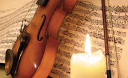 Violin on music sheet behind a candle Royalty Free Stock Image
