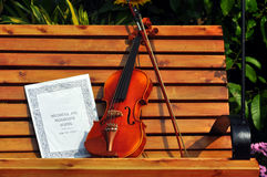 Violin and musical note on bench Stock Photo