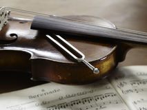 Violin, musical notes and tuning fork. Lying on violin Stock Image