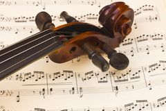 Violin neck over a music score sheet royalty free stock photography