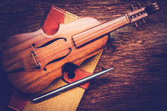 Violin and notebook with pen on grunge dark wood background. Stock Photos