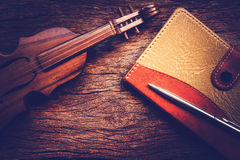Violin and notebook with pen on grunge dark wood background Royalty Free Stock Images