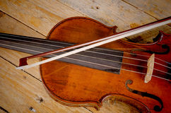 Violin. Old violin and arch on a wooden background Royalty Free Stock Photo