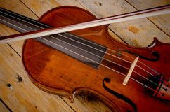 Violin. Old violin and arch on a wooden background Stock Images