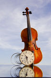 Violin with old clock on mirror Stock Photo