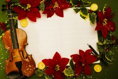 Violin and open music manuscript on the green background. Christmas concept Royalty Free Stock Photo