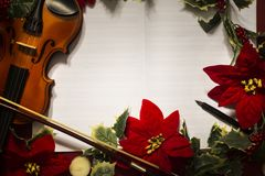 Violin and open music manuscript on the red background. Christmas concept stock image