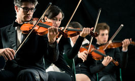 Violin orchestra performing. On stage on dark background royalty free stock image