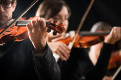 Violin orchestra performing on stage Stock Images