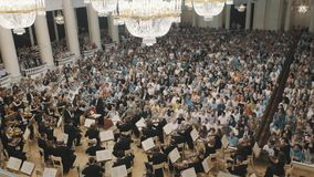 Violin orchestra playing on scene of old concert hall in front of lots of people stock footage