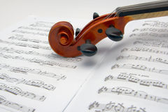 Violin over music scores. Violin neck resting over a sheet music Stock Photo