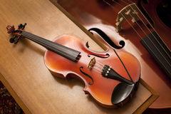 A violin on a piano bench Royalty Free Stock Images